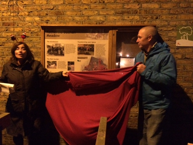 Trust members unveil the Katherine Buchan Meadow panel at the Christmas party